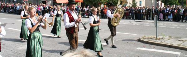 Oktoberfest girls in dirndl dress playing brass music